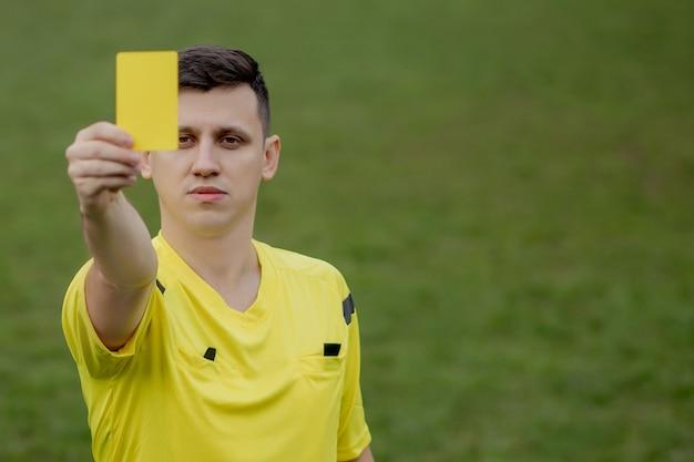 Schiedsrichter, der einem unzufriedenen fußball- oder fußballspieler während des spiels eine gelbe karte zeigt. konzept des sports, regelverletzung, kontroverse themen, überwindung von hindernissen.