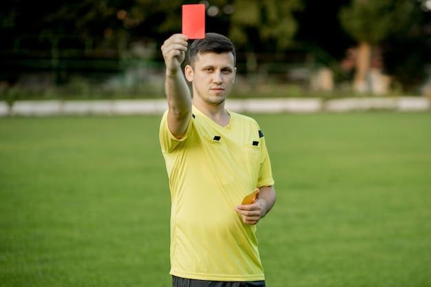 Schiedsrichter, der einem unzufriedenen fußball- oder fußballspieler während des spiels eine rote karte zeigt. konzept des sports, regelverletzung, kontroverse themen, überwindung von hindernissen.