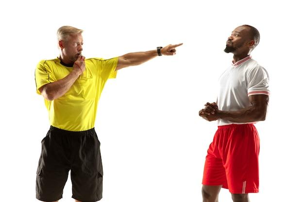 Schiedsrichter gibt fußball- oder fußballspielern anweisungen mit gesten, während sie isoliert auf weißer wand spielen.