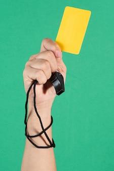 Schiedsrichter hand mit einer gelben karte und pfeife auf grünem hintergrund.