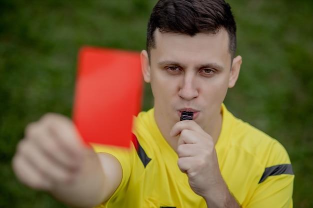 Schiedsrichter zeigt einem unzufriedenen fußball- oder fußballspieler beim spielen eine rote karte. konzept des sports, regelverstoß, kontroverse themen, überwindung von hindernissen.