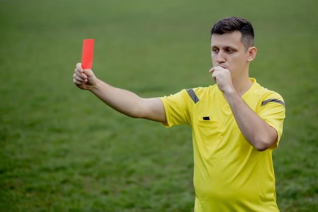 Schiedsrichter zeigt einem unzufriedenen fußball- oder fußballspieler beim spielen eine rote karte.