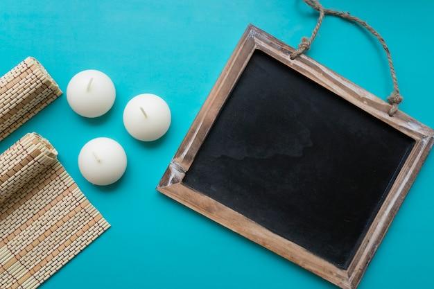 Schiefer, kerzen und bambus tuch auf blauem hintergrund