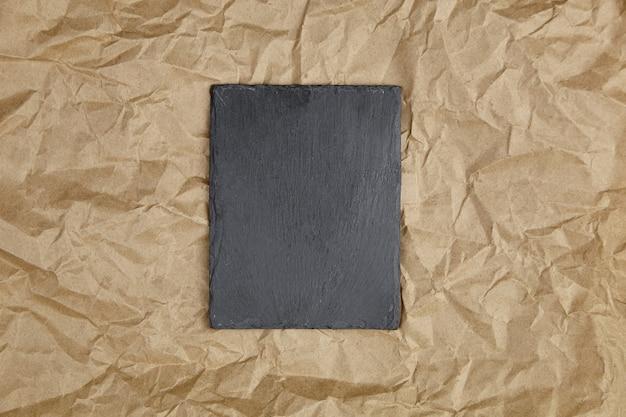 Schieferbrett auf zerknittertem bastelpapier