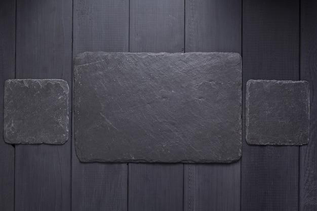 Schieferstein-typenschild oder wandschild auf schwarzer holzhintergrundtexturoberfläche, mit schrauben