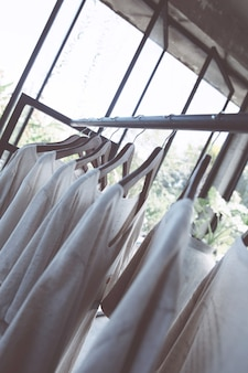 Schiene mit weißen t-shirts auf kleiderbügeln im laden. lässige sommerkleidung