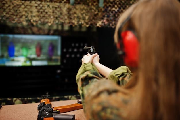 Schießen am schießstand. die frau am schießstand schoss aus der pistole.