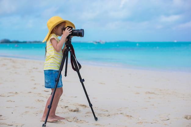 Schießen des kleinen mädchens mit kamera auf einem stativ während ihrer sommerferien