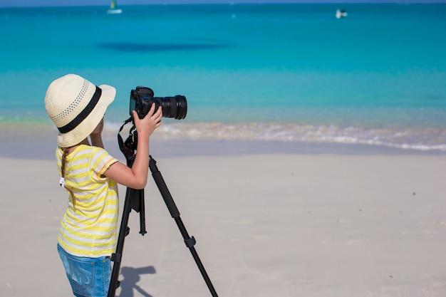 Schießen des kleinen mädchens mit kamera auf stativ während ihrer sommerferien