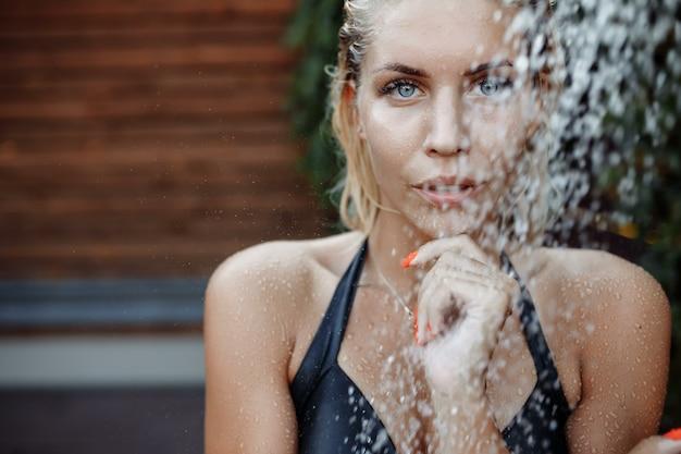 Schießen im aquazon mit fallenden wassertropfen. ein mädchen mit blonden haaren in einem schwarzen badeanzug unter einer kalten dusche in einem erholungskomplex. sommerferien-werbekonzept am pool, wasserpark.