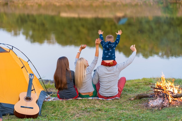 Schießen sie von hinten. eine gruppe glücklicher freunde mit kind auf der schulter kampierend am flussufer, tanzen halten hände hoch und genießen ansicht. familienurlaub spaß