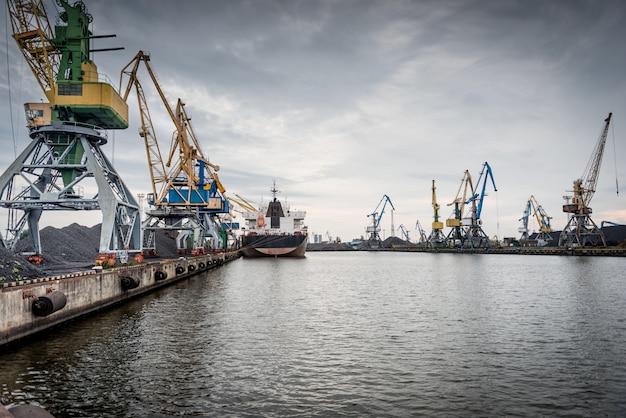 Schiffe und kräne an einem hafenterminal