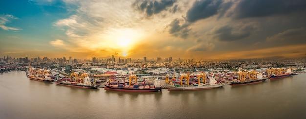 Schifffahrtshafen am flussufer in der stadt bei sonnenuntergang von drohne genommen