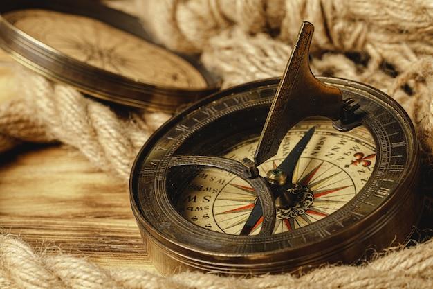 Schiffsseil und kompass auf holz Premium Fotos