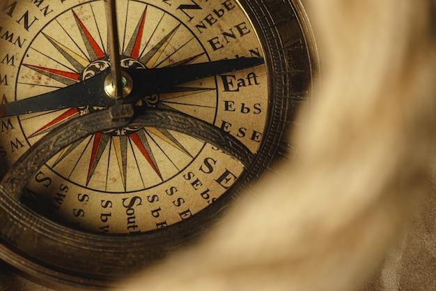 Schiffsseil und kompass auf holztisch, nahaufnahme