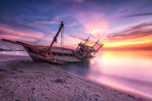 Schiffswrack am strand in der dämmerung zeit