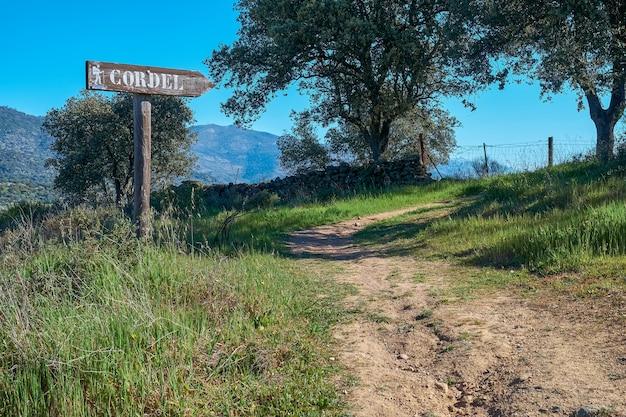 Schild aus holz, das den weg eines heute zum wandern genutzten viehweges anzeigt