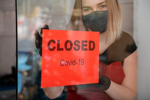 Schild geschlossene covid 19-sperre an der eingangstür des geschäfts als neue normale abschaltung. frau in medizinischen schutzmaskenhandschuhen hängt geschlossenes schild am fenster des café-restaurants. lockdown-coronavirus covid 19.