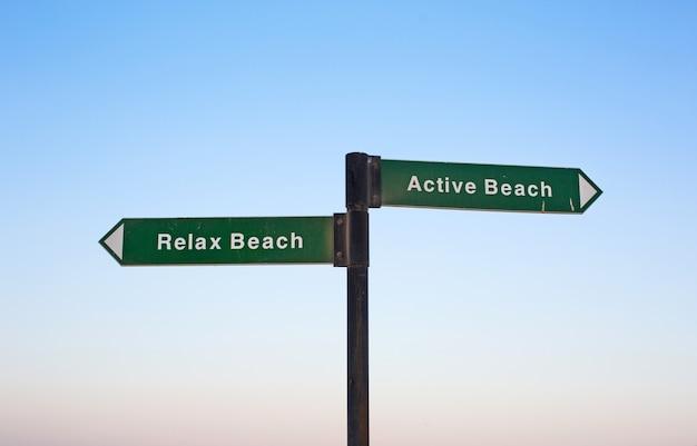 Schild mit pfeilen - strand entspannen und aktiver strand am himmelshintergrund