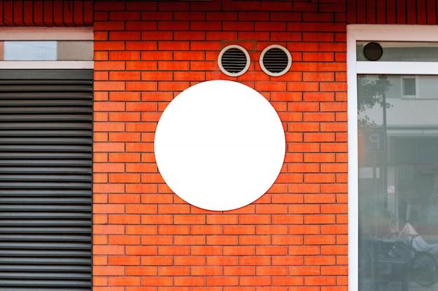 Schildspeicherplanlogodesign-kreisschablone auf wand des roten backsteins.