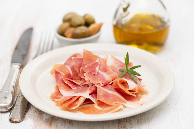 Schinken auf teller mit olivenöl und oliven