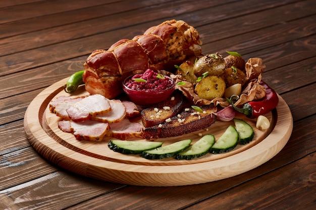 Schinken garniert mit gemüse, obst und kräutern mit saucen und brot auf einem holzteller auf einem dunklen holztisch.