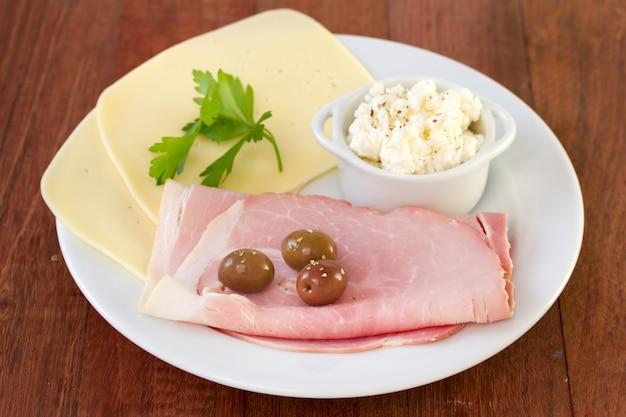 Schinken mit käse, oliven auf teller