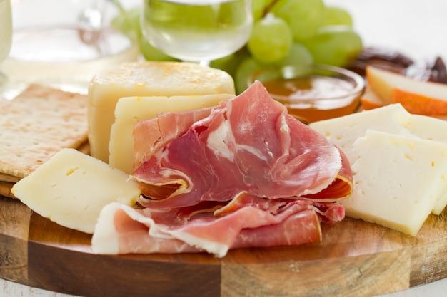 Schinken mit käse, trauben und weißwein
