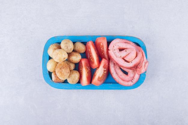 Schinkenröllchen, tomaten und bratkartoffeln auf blauem teller.