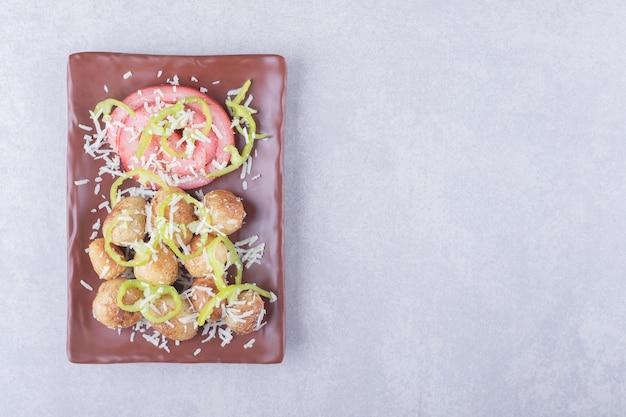 Schinkenröllchen und bratkartoffeln auf dunklem teller.