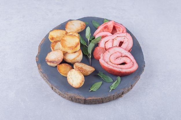 Schinkenröllchen und bratkartoffeln auf holzstück.