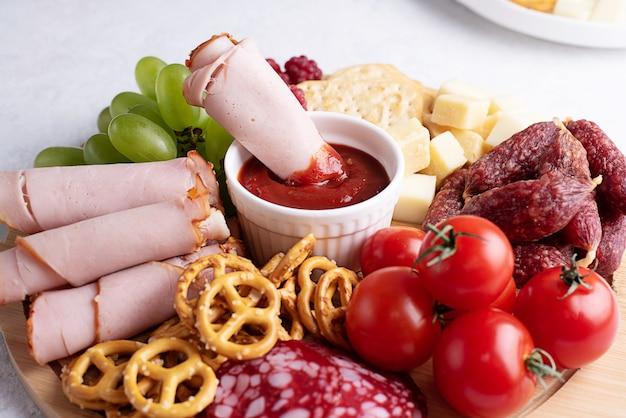 Schinkenscheibe in soße auf wurstbrett mit wurst, käse, crackern und obst, teller mit vorspeise, nahaufnahme.