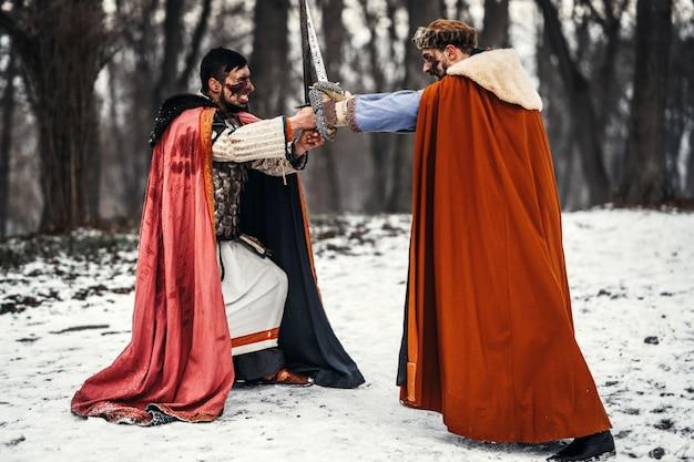 Schlacht zweier ritter in bunten gewändern und hüten in der nähe von wald und holzfestung. ritter kämpfen im winter im schnee