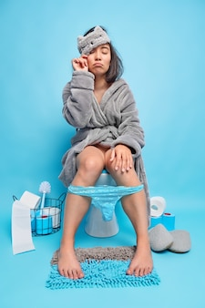 Schläfrige asiatin wacht früh morgens auf, kommt in die toilette und sitzt auf der toilette