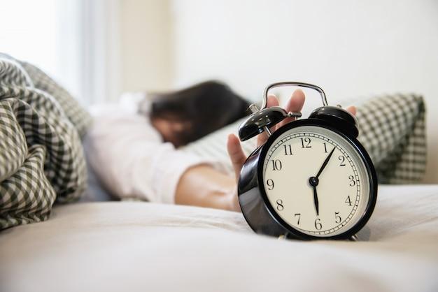 Schläfrige frau, die den wecker halten erreicht