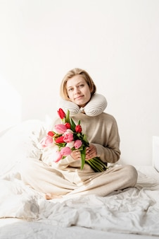Schläfrige frau, die im bett sitzt und pyjama und kissen über dem hals trägt, tulpenblumen auf dem bett