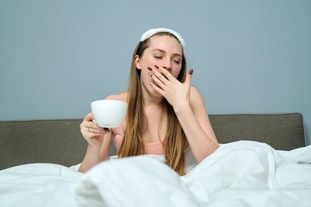 Schläfrige gähnende junge frau im bett mit tasse tee