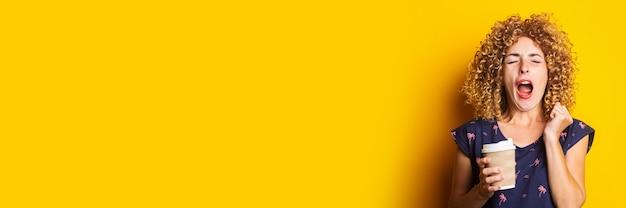 Schläfrige gähnende junge frau mit dem lockigen haar, das pappbecher auf gelber oberfläche hält