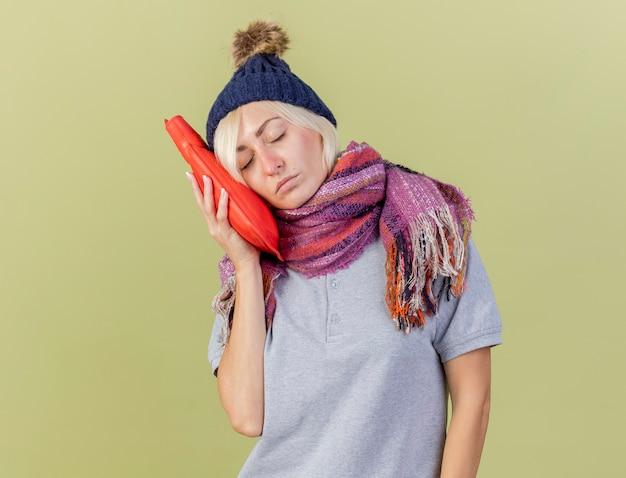 Schläfrige junge blonde kranke slawische frau, die wintermütze und schal trägt, setzt kopf auf wärmflasche lokalisiert auf olivgrüner wand mit kopienraum