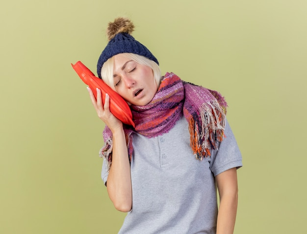 Schläfrige junge blonde kranke slawische frau, die wintermütze und schal trägt, steht mit geschlossenen augen, die kopf auf wärmflasche setzen, lokalisiert auf olivgrüner wand mit kopienraum