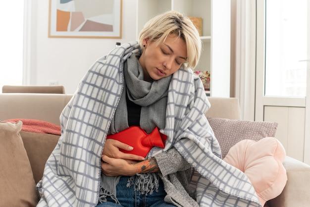 Schläfrige junge kranke slawische frau mit schal um den hals, die in plaid gewickelt ist und wärmflasche hält, die auf der couch im wohnzimmer sitzt