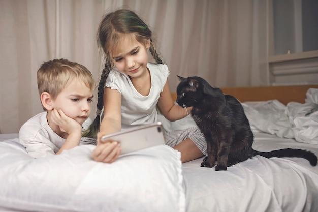 Schläfrige kinder im pyjama schauen sich ein video auf dem smartphone im bett an und kämpfen abends ums schlafen