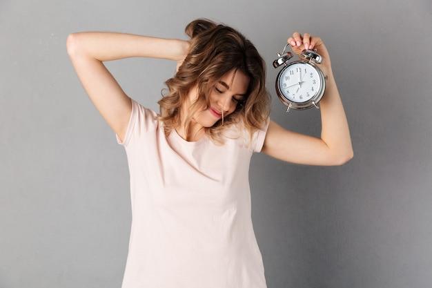 Schläfrige lächelnde frau im t-shirt wachen auf, während sie wecker mit geschlossenen augen über grau hält