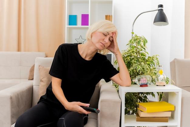 Schläfrige schöne blonde russische frau sitzt auf sessel, der hand auf kopf hält, die tv-fernbedienung im wohnzimmer hält