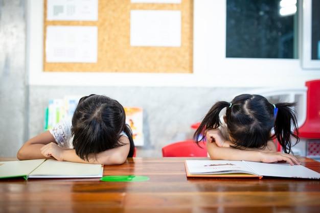 Schläfrige schüler, die an den schreibtischen im klassenzimmer an der grundschule nickerchen machen