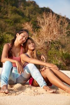 Schläfrige verträumte mischlingsfrauen sitzen am sandstrand