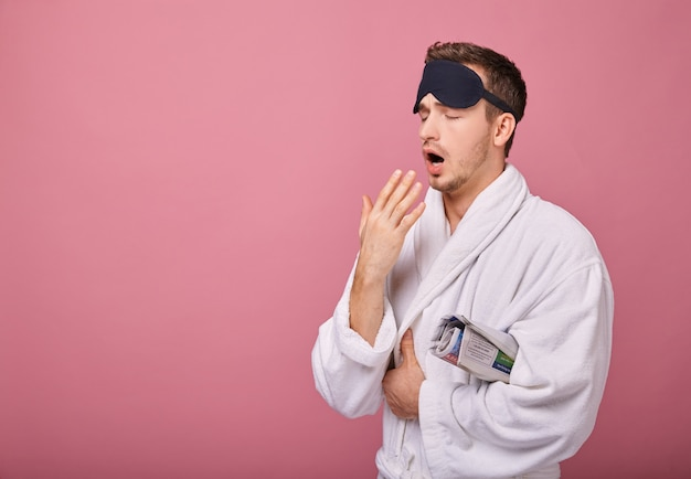 Schläfriger cooler typ in schlafmaske auf dem kopf im weißen kittel mit gebundenem gürtel gähnt
