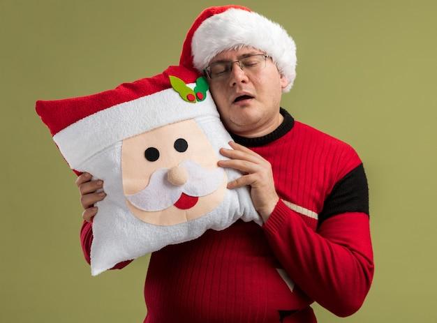 Schläfriger erwachsener mann, der brille und weihnachtsmütze trägt, die weihnachtsmannkissenkissen berührend kopf mit ihm schlafend isoliert auf olivgrünem hintergrund hält