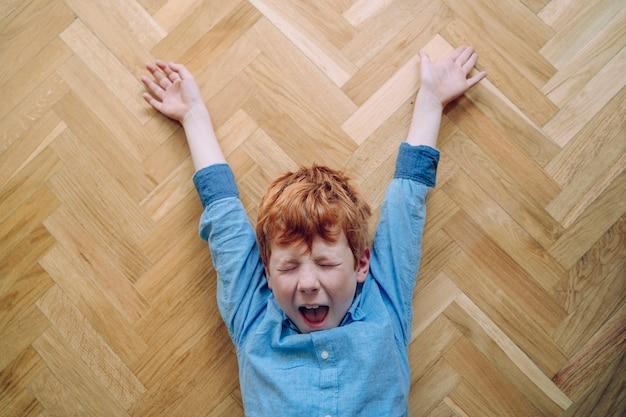 Schläfriger gelangweilter kleiner junge auf dem hausboden, der ein großes gähnen mit weit geöffnetem mund macht.