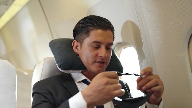 Schläfriger geschäftsmann reisen auf einer geschäftsreise mit dem flugzeug. executive traveller konzept.